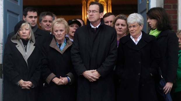Connecticut Gov. Dan Malloy, centre, stands with other officials to observe a moment of silence while bells ring 26 times in Newtown, Conn., on Friday, Dec. 21, 2012, in honor of the victims who were killed in the Sandy Hook Elementary School shooting. (AP Photo/Seth Wenig)