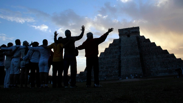 People gesture toward the the Kukulkan temple in Chichen Itza, Mexico on Friday, Dec. 21, 2012. (AP Photo/Israel Leal)