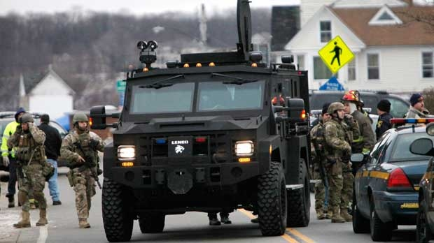 A Monroe County Sheriff's Department armored truck drops off residents who were evacuated from the neighborhood, Monday, Dec. 24, 2012 in Webster, New York. (AP Photo/Democrat & Chronicle, Max Schulte)