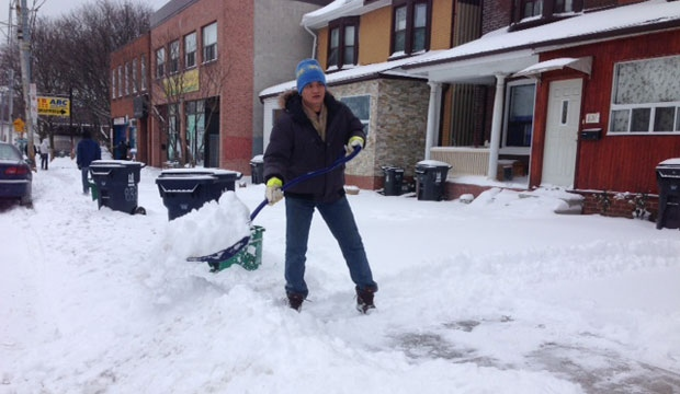 In this file photo, a man shovels snow outside a home on Gerrard Street after a winter storm. (Cam Woolley/CP24)
