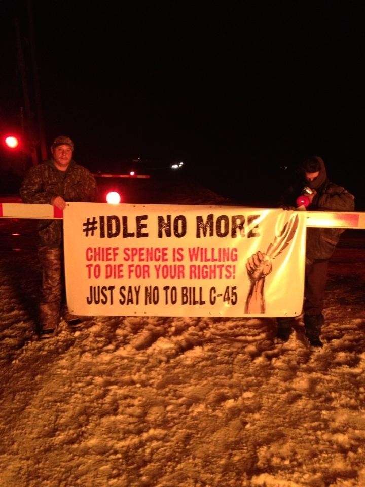 Protesters carry placards at a protest blocking Via Rail trains near Belleville Sunday, December, 30, 2012.