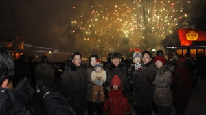A North Korean family has their photo taken in front of fireworks as they celebrate the New Year in Pyongyang on Tuesday, Jan. 1, 2013. (AP Photo/Kim Kwang Hyon)