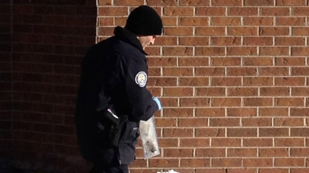 A police officer carries a bag containing evidence at the scene of a fatal stabbing on Keele Street on Tuesday, Jan. 1, 2013. (George Lagogianes/CP24)