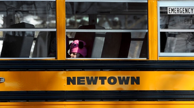 A child sits on a Newtown bus leaving the new Sandy Hook Elementary School on the first day of classes in Monroe, Conn., on Thursday, Jan. 3, 2013.  (AP Photo/Jessica Hill)