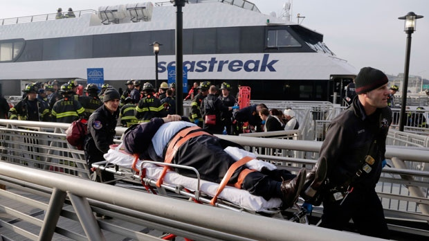 An injured passenger from the Seastreak Wall Street ferry is taken to an ambulance in New York, on Wednesday, Jan. 9, 2013. (AP Photo/Richard Drew)