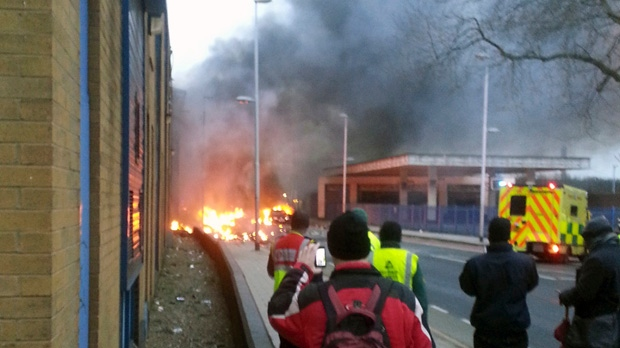 People gather shortly after a helicopter crashed in the Vauxhall area of central London after hitting a crane on top of a tower block near the River Thames on Wednesday, Jan. 16, 2013. (AP Photo/Toby Scott, PA)