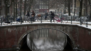 Cyclists cross a snow-covered bridge in the centre of Amsterdam, Netherlands on Monday Jan. 21, 2013. (AP Photo/Peter Dejong)