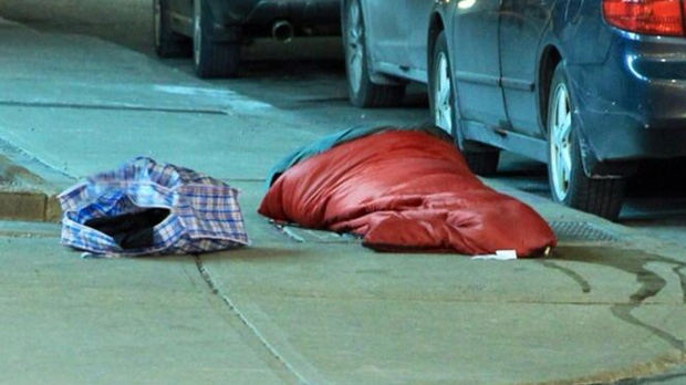 A homeless person sleeps on a sidewalk in downtown Toronto during an extreme cold weather alert early Tuesday, Jan. 22, 2013. (Tom Stefanac/CP24)