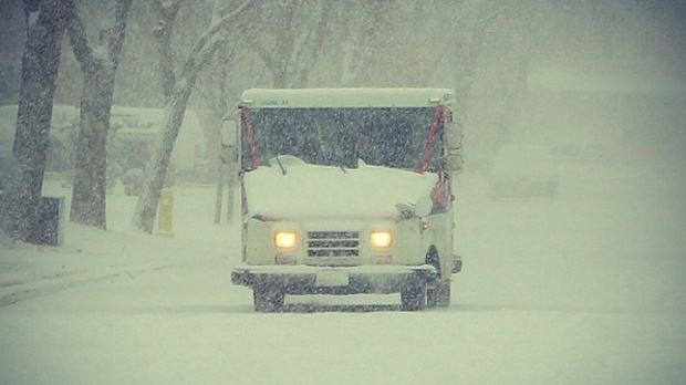A vehicle makes its way along a snowy street in Vaughan on Tuesday, Jan. 22, 2013. (Tom Stefanac/CP24)