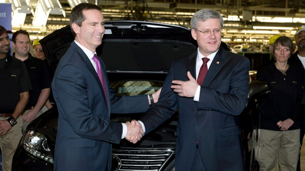 Ontario Premier Dalton McGuinty, left, and Prime Minister Stephen Harper shake hands after attaching the final parts to a Lexus SUV at the Toyota automotive plant in Cambridge, Ont., on Wednesday, Jan. 23, 2013. (The Canadian Press/Frank Gunn)
