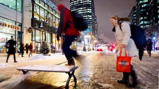 Pedestrians use a city bench to cross a flooded street in Montreal on Monday, Jan. 28, 2013, following a water main break. (The Canadian Press/Graham Hughes)
