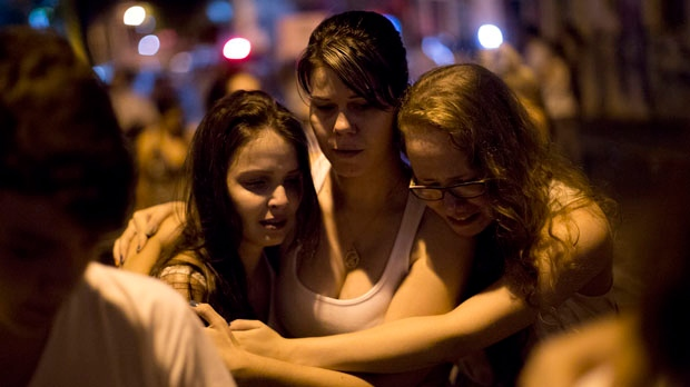 People react during a march near the Kiss nightclub in Santa Maria, Brazil on Monday, Jan. 28, 2013, as they honour the victims of a fatal fire. (AP Photo/Felipe Dana)
