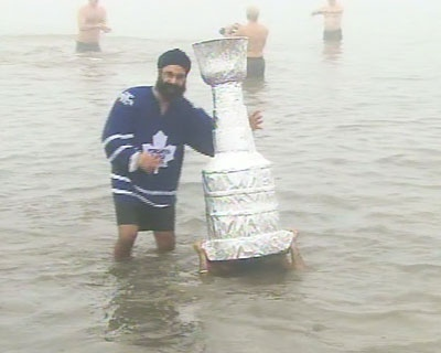 A man carrying a Stanley Cup replica submerges himself in Lake Ontario on Saturday, Jan. 1, 2011, while another Polar Bear Dip participant looks on.