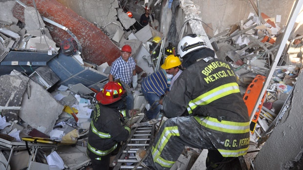 Firefighters belonging to the Tacubaya sector and workers dig for survivors after an explosion at an adjacent building to the executive tower of Mexico's state-owned oil company PEMEX, in Mexico City, on Thursday, Jan. 31, 2013. (AP Photo/Guillermo Gutierrez)