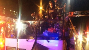 In this photo released by the Boston Fire Department via Twitter, firemen work to remove injured passengers from a bus that hit an bridge as it traveled along Soldiers Field Road in the Allston neighborhood of Boston Saturday night, Feb. 2, 2013. Officials said the bus carrying 42 people was traveling from Harvard University home to Pennsylvania when it struck the overpass. (AP Photo/Boston Fire Department)
