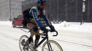 A bicycle courier wears shorts and ski goggles as he rides through a snow storm in downtown Toronto on Friday, Feb. 8, 2013. (The Canadian Press/Frank Gunn)