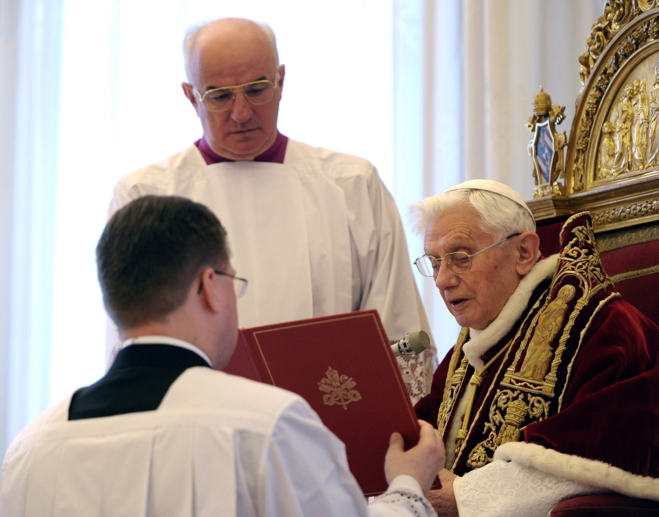 In this photo provided by the Vatican newspaper L'Osservatore Romano, Pope Benedict XVI, right, delivers a message during a meeting of Vatican cardinals at the Vatican on Monday, Feb. 11, 2013. (AP Photo/L'Osservatore Romano, ho)
