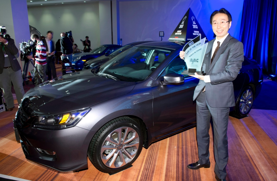 Takashi Sekiguchi, president and CEO of Honda Canada Inc., holds the Automotive Journalists Association of Canada award for the 2013 Canadian car of the year at the Canadian International Auto Show in Toronto on Thursday, Feb. 14, 2013. (The Canadian Press/Frank Gunn)