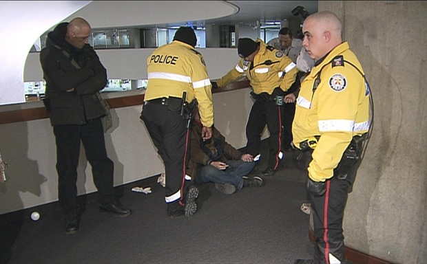 Toronto police speak to a protester before leading them out of City Hall where about 50 people staged a day-long demonstration to call attention to the lack of homeless beds in the city.