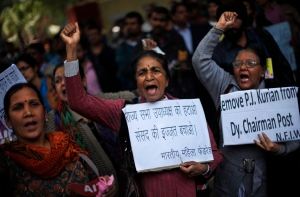 Protesters hold placards near India's parliament to protest a new sexual violence law as the parliament convenes in New Delhi, India on Thursday, Feb. 21, 2013. (AP Photo/Altaf Qadri)