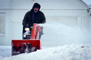 Chris Peacock clears his neighbor's driveway in Des Moines, Iowa on Friday, Feb. 22, 2013, after an overnight snowstorm. (AP Photo/The Des Moines Register, Rodney White)