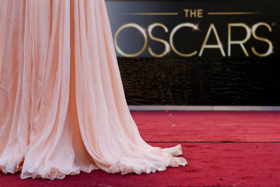 A television reporter from Mexico is silhouetted as she reports from the red carpet outside the Dolby Theatre in the Hollywood section of Los Angeles on Feb. 22, 2013. (AP / Jae C. Hong)