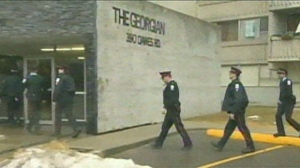 Police are shown entering an apartment building on Dawes Road near Victoria Park Avenue Saturday morning. A 25-year-old man is being treated in hospital after he was stabbed in the torso inside the building.