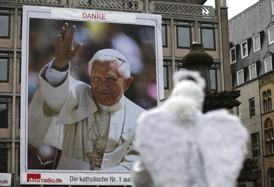 An artist dressed as an angel poses for tourists in front of a huge Pope Benedict XVI poster in Cologne, Germany on Tuesday, Feb. 26,2013. (AP Photo/Frank Augstein)