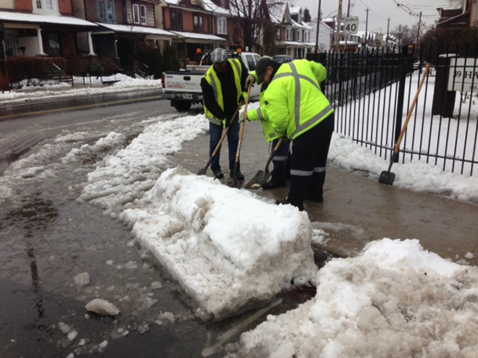 City of Toronto employees clear a drain that was clogged on Pape Avenue after a winter storm swept through the city Wednesday, Feb. 27, 2013. (Cam Woolley/CP24)