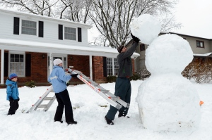 Brandon Rink, 6, watches as his mother Susan holds a ladder as his father David pushes the head of their giant snowman into place on Wednesday, Feb. 27, 2013 on Glenn Leven Rd. in Ann Arbor, Mich. The family, along with siblings Justin, 8 and Chloe, 3, started building the snowman the night before creating the base out snow from the driveway. (AP Photo/AnnArbor.com, Melanie Maxwell)