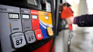 A motorist reaches for the pump at a gas station in Toronto (Patrick Dell/The Canadian Press)
