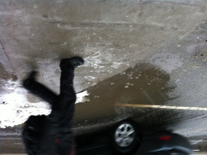 A pedestrian encounters a large slushy puddle walking along Queen Street in downtown Toronto Wednesday, Feb. 27, 2013. A mixture of snow and rain brought on by a winter storm made for slippery walking conditions in the city. (CP24/ Joshua Freeman)
