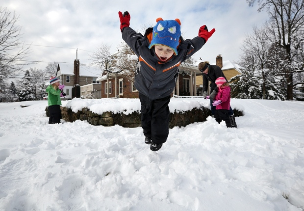 Johnny Connell, 5, takes a dive into the snow while his twin sisters Christine and Sammy, 3, and mother Megan Connell play in the yard across from their home in Clintonville, Ohio on Wednesday, March 6, 2013. (AP Photo/The Columbus Dispatch, Adam Cairns)