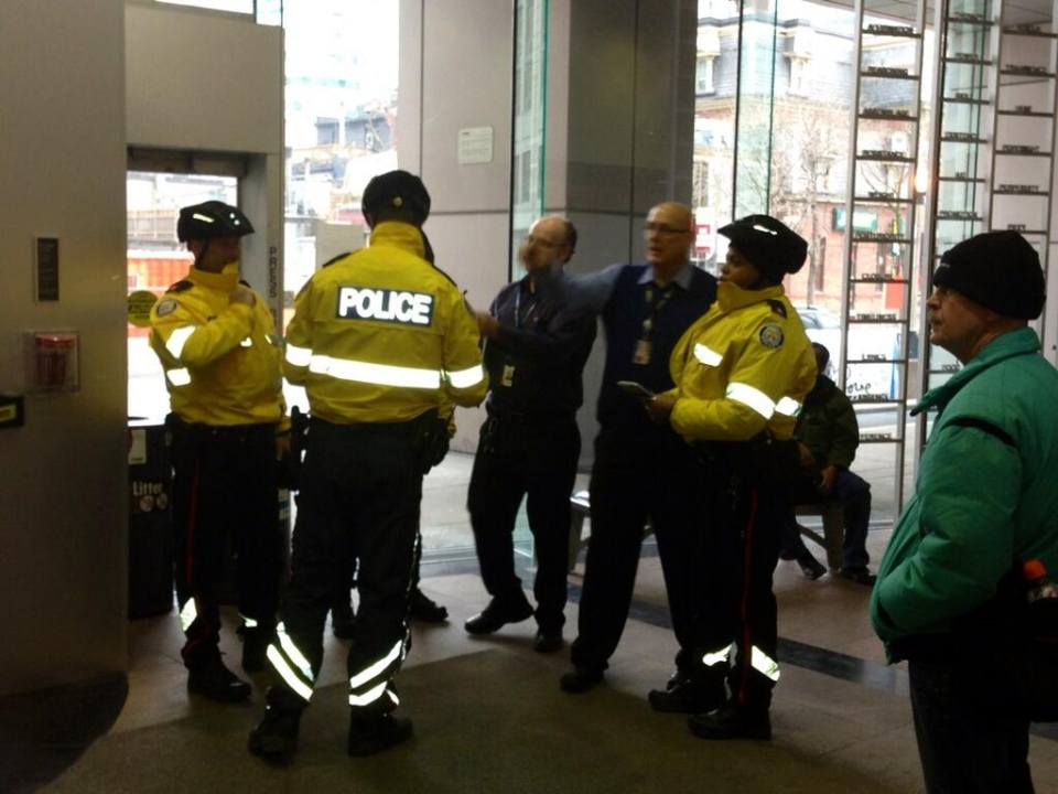 Police and security guards convene in Metro Hall ahead of the expected arrival of anti-poverty activists on Thursday, March 7, 2013. (Cristina Tenaglia / CP24)