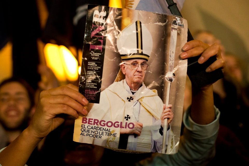 A worshiper holds up the front page of a magazine showing a photograph of Jorge Mario Bergoglio with the title in Spanish