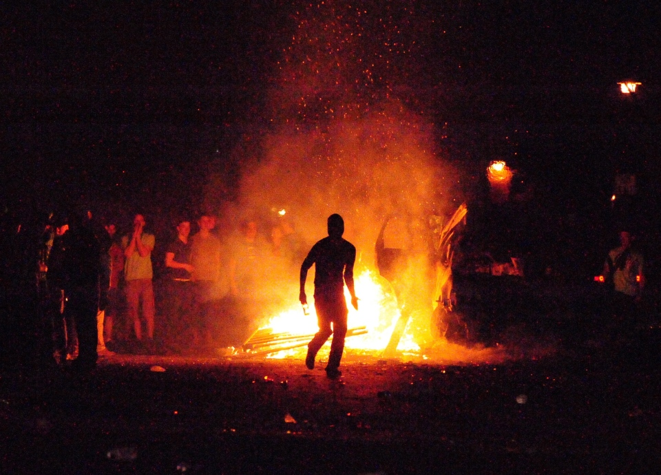 A lone rioter is silhouetted by a fire as he prepares to throw a glass bottle at police during a riot on London, Ont., early Sunday, March 18, 2012. (The Canadian Press/London Community News-Mike Maloney)