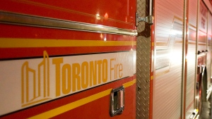 A Toronto Firefighter walks past a fire truck in Toronto on Thursday night, April 21, 2011. (Aaron Vincent Elkaim / THE CANADIAN PRESS)