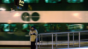 A woman reads a book as a GO commuter train pulls away from the platform at Toronto's Union Station, March 4, 2008. (J.P. Moczulski / THE CANADIAN PRESS)
