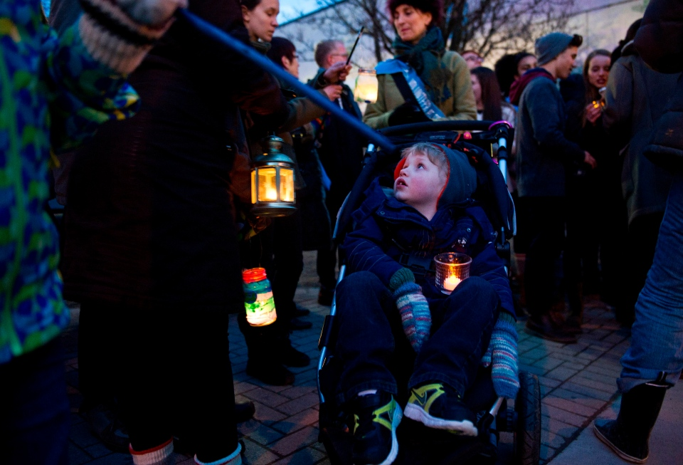 Three-year-old Brayden Elliot glances up as he waits for the WWF-Canada Earth Hour lantern walk to begin in Roncesvalles Village Toronto on Saturday, March 23, 2013. (Galit Rodan/ THE CANADIAN PRESS)