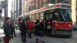 People exit and board a TTC streetcar on Queen Street. (Chris Kitching/CP24)