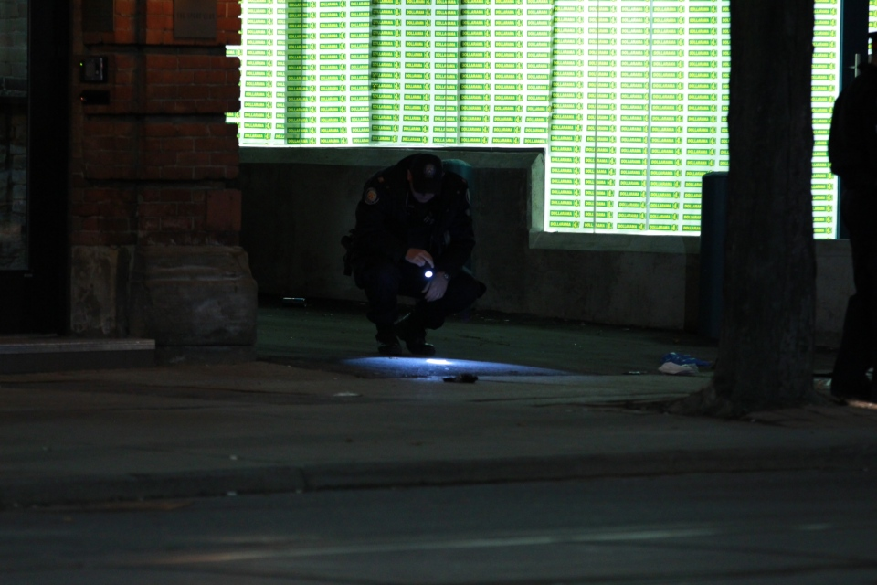 A police officer is shown at the scene of a double shooting on King Street near Bathurst Street early on March 28, 2013. (Tom Stefanac)