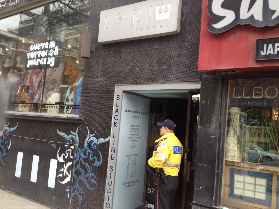 A police officer stands in the doorway of Loki Lounge on Thursday, March 28, 2013, following a fatal shooting on King Street earlier in the morning. (CP24/Nneka Elliot)