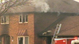 Smoke is seen billowing from a home that caught fire in East Gwillimbury on March 29, 2013.