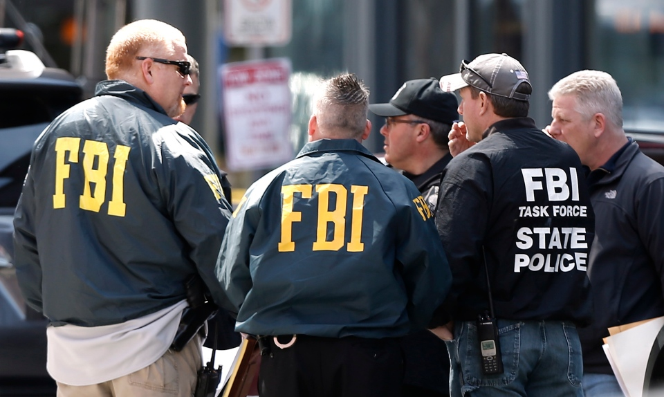 FBI agents gather near the finish line of the Boston Marathon in Boston on Tuesday, April 16, 2013, a day after a deadly bombing. (AP Photo/Winslow Townson)