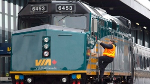 A Via Rail employee climbs aboard a locomotive at the train station in Ottawa on Monday, Dec. 3, 2012. (The Canadian Press/Adrian Wyld)