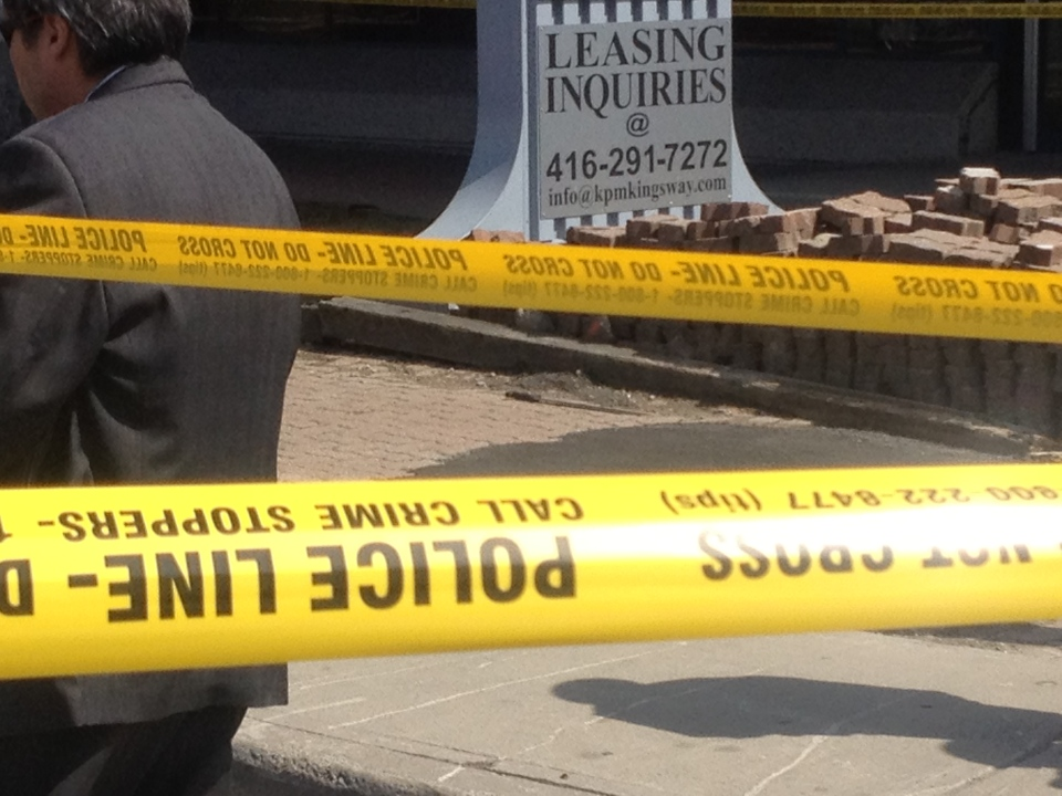 Police tape and what appears to be a machete lying in the ground are seen in this photograph after a man was shot and killed by Toronto police in the city's east end on Friday, April 26, 2013. (CP24/Nneka Elliot)