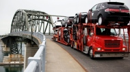 In this June 1, 2009 file photo, a truck loaded with Ford and Lincoln vehicles travels from Canada to the U.S. Peace Bridge border crossing in Buffalo, N.Y. (AP / David Duprey)