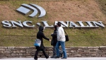 Pedestrians walk past the offices of SNC Lavalin, in Montreal, March 26, 2012. THE CANADIAN PRESS/Ryan Remiorz