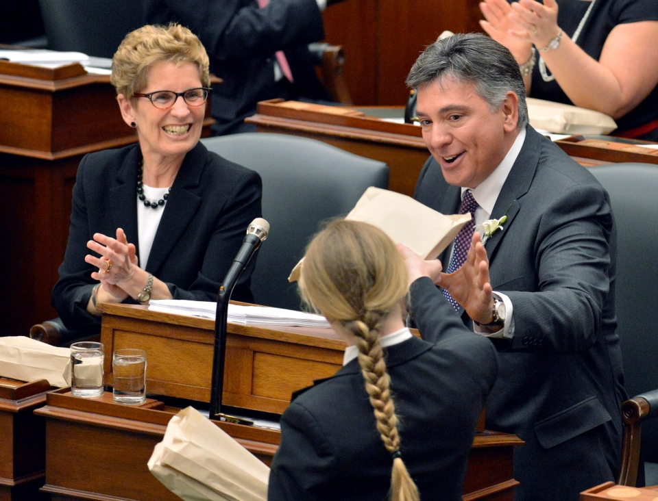 Ontario Premier Kathkleen Wynne applauds as Finance Minister Charles Sousa is handed a copy of the 2013 provincial budget at Queen's Park in Toronto on Thursday, May 2, 2013. (The Canadian Press/Nathan Denette)