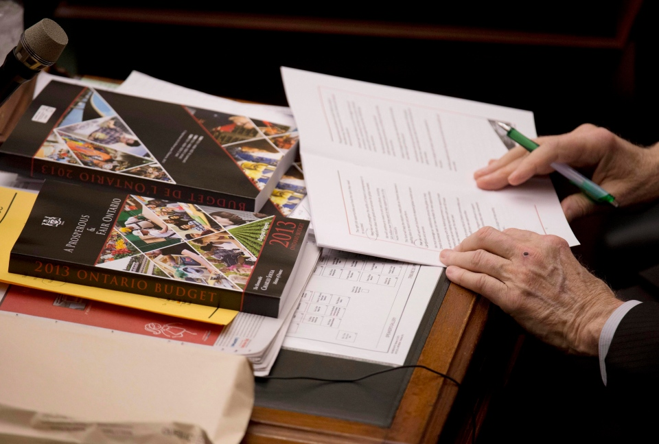 An Ontario MPP looks over a copy of the 2013 provincial budget at Queen's Park in Toronto on Thursday, May 2, 2013. (The Canadian Press/Nathan Denette)